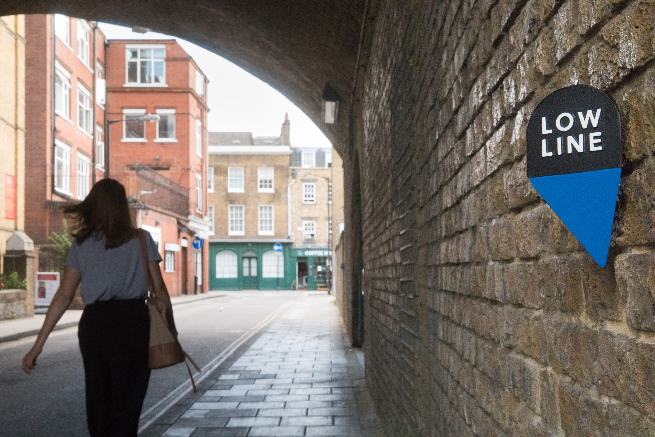 Image of a woman walking under an arch with the low line marker in the foreground